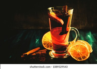 Christmas mulled wine, cinnamon sticks, anise star, orange dried, dark toned background.