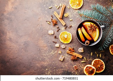 Christmas mulled wine or gluhwein with spices and orange slices on rustic table top view. Traditional drink on winter holiday. Copy space for recipe.