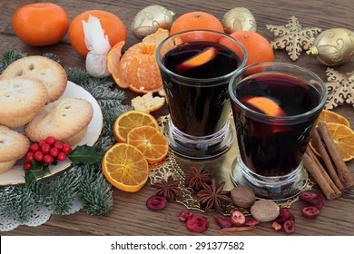 Christmas mulled wine, mince pies, spices, fruit, baubles and winter greenery over oak background.