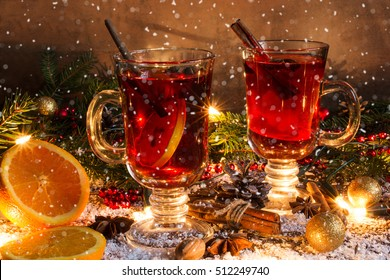 christmas mulled wine with snow and decorations in christmas lights on wooden background