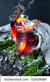 Christmas mulled wine with spices in glasswith plaid and snow on a christmas tree on dark background