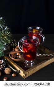 Christmas mulled wine in wooden tray with fir branches on a dark background , copy space