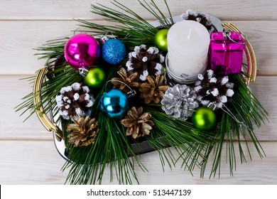 Christmas multicolored ornaments and candle centerpiece. New year greeting background with pine cones.
