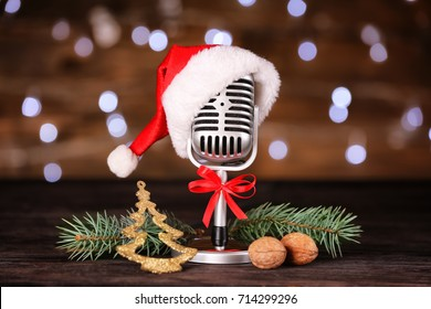 Christmas music concept. Microphone with hat and decoration on wooden table