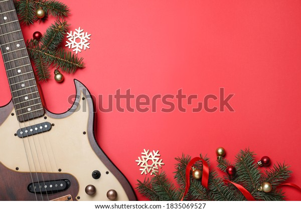 Christmas music. Flat lay composition with guitar and fir tree branches on red background, space for text