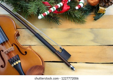 Christmas music theme with violine and bow on a rustic wooden background. Christmas decorations on one border. Copy space