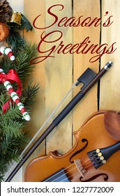 Christmas music theme with violine and bow on a rustic wooden background. Christmas decorations on one border. Vertical iimage with seasonal message added
