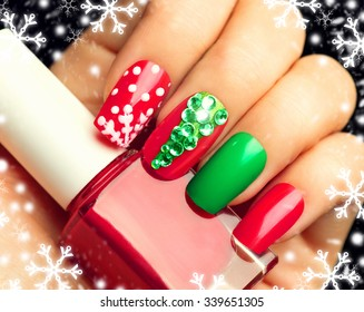 Christmas Nail art manicure. Winter Holiday style bright Manicure with gems Christmas tree and snowflakes. Bottle of Nail Polish. Beauty hands. Trendy Stylish Colorful Nails, Nailpolish