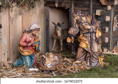 Christmas nativity scene - Jesus Christ, Mary and Joseph. Wooden figurines, donkey in the background.