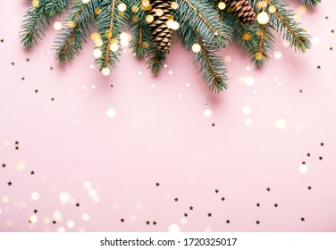 Christmas natural coniferous border with cones and confetti. Festive pink background with sparkles and bokeh lights.