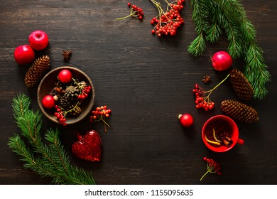 Christmas natural decor stuff on moody rustic table top ready for setting a dinner table, cup of winter warmer standing below, cones, fruits and winter berries around the center