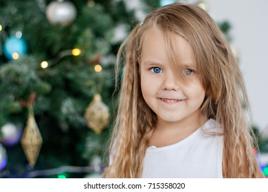 Christmas and New Year 2018. Portrait of a little girl near the Christmas tree in anticipation of a miracle, gifts and Santa Claus