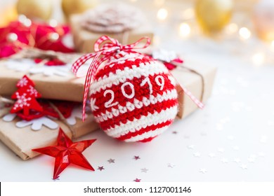 Christmas and New Year 2019 background with crocheted handmade ball, presents and decorations for Christmas tree. Holiday background with stars confetti and light bulbs. Place for text.