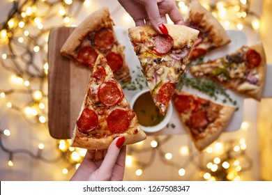 Christmas and New Year atmosphere. Womans hand takes slice of Italian pizza with melting tomato, pepperoni and cheese on a white marbel cutting board. Background with lights in bokeh and selective