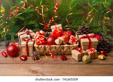 Christmas or New Year background: basket with colored glass toys and balls, decoration and gifts on wooden background