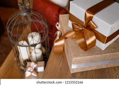 Christmas or New Year background: candele, wooden wall, golden and brown gifts