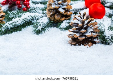 Christmas and New Year background with Christmas candle and Christmas tree branches on snow and decorations. Free space
