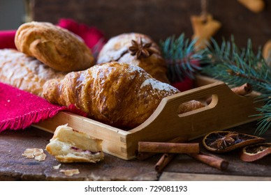 Christmas and New Year background with continental breakfast - cinnamon fresh orange and croissant. Decorations -  napkin pine cones.