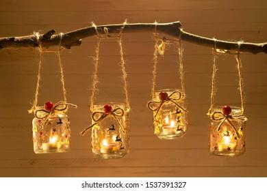 Antecedentes navideños decorados con velas en tarros de vidrio reciclados