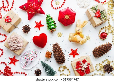 Christmas and New Year background with decorations. Gifts in craft paper, pine cones, red hearts and confetti. Flay lay, top view.