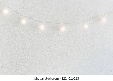Christmas New Year Background. Diagonal Hanging Pastel Golden Cotton Balls Garland White Wall Background. Scandinavian Style. Glittering Lights. Cozy Festive Atmosphere. Poster with Copy Space