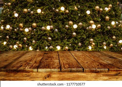 Christmas and New year background with empty wooden deck table over blurred christmas tree at night. Empty display for product montage. Rustic scene.