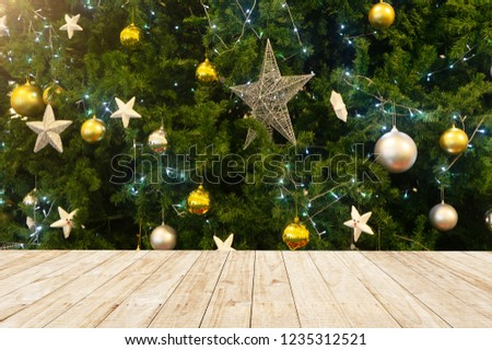 christmas and new year background with empty dark wooden deck table over christmas tree