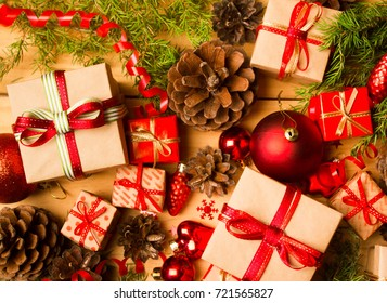 Christmas or New Year background: fir tree branches, red glass balls, gift, decoration and cones on a wooden background
