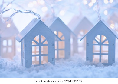 Christmas and New Year background with a garland in the form of little houses on the snow