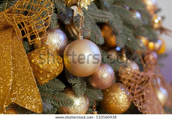 Christmas and New year background with green Tree decorated with toys . Gold .