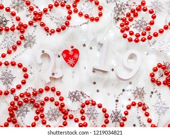 Christmas and New Year background with numbers 2019, red heart, silver decorations and light bulbs.