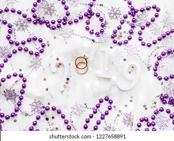 Christmas and New Year background with numbers 2019, wedding rings with diamond, violet decorations and light bulbs.