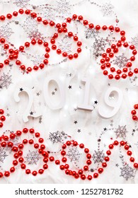 Christmas and New Year background with numbers 2019, red decorations and light bulbs.