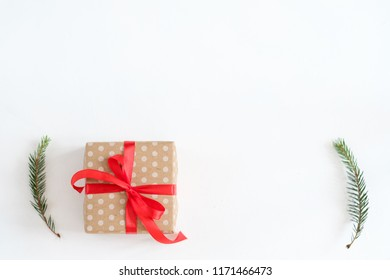 christmas and new year background. present wrapped in dotted craft paper and tied with red ribbon on white backdrop. handcrafted gift and fir tree branches decor.