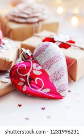 Christmas and New Year background with presents and decorative heart for Christmas tree. Holiday background with stars confetti and light bulbs. Place for text.