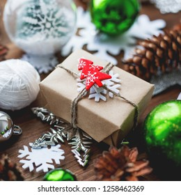 Christmas and New Year background with presents, ribbons, balls and different green decorations on wooden background. Gift packed in craft paper with red fir tree.