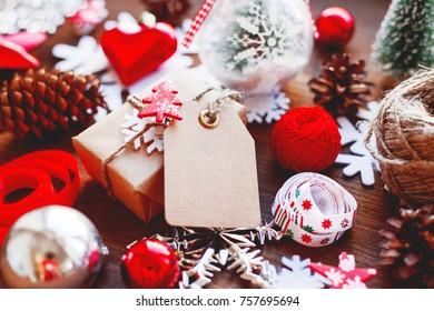 Christmas and New year background with presents, ribbons, balls and different decorations on wooden background. Gift with toy fir tree and clear tag for your text. Mock up.
