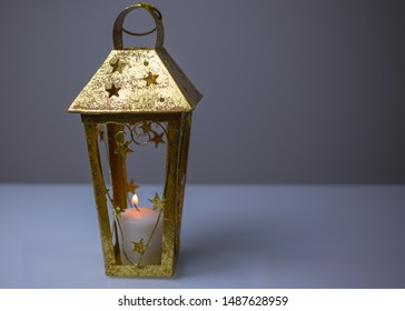 Christmas and New Year background with vintage Christmas golden metal candle lantern with stars and heart and burning candle inside