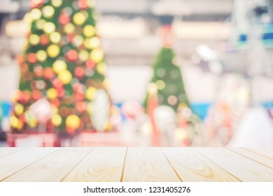 Christmas and New year background,Wood table top with blurred decoration chrismas tree and  bokeh background ,can be used for display or montage your products