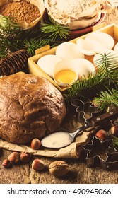 Christmas or New Year baking cookies background. Dough, dough ingredients - flour, chocolate, walnuts, hazelnuts, sugar eggs cinnamon and Christmas decorations on wooden rustic background