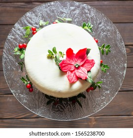 Christmas or New Year cake covered with mirror glaze, decorated with lingonberry, leaves and mastic poinsettia flower. Modern European cake. French cuisine.