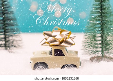 Christmas or New year card with toy car with golden bow and christmas tree miniatures and bokeh lights on background. Merry chritmas quote