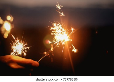 Christmas and new year celebration background concept : Blurred woman hand holding bright burning Christmas sparkle on nature landscape night sky background.Winter night film grain filter effect.