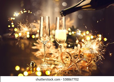Christmas and New Year celebration with champagne. New Year holiday decorated table. Two Champagne Glasses, vintage toned.