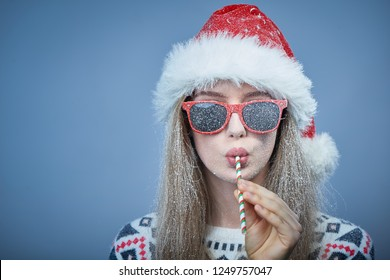 Christmas or New Year celebration. Closeup of frozen girl with snow on face wearing Santa hat and sunglasses, drinking through a straw, portrait with copy space