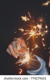 Christmas and new year celebration concept : Abstract Blurred close up woman hand holding bright burning Christmas sparkle on winter night background.Winter night vintage film grain filter effect.