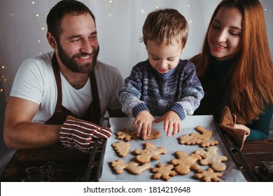 Christmas and New Year celebration. Family time. Holidays. Little boy and parents with gingerbread cookies.