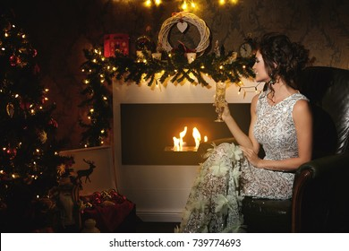 Christmas or New year celebration. Happy woman sitting in the armchair with a glass of champagne