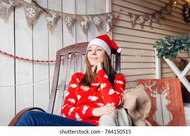 Christmas or New Year celebration. Happy woman sitting in the rocking chair. looking off to the side. the Santa Claus hat
