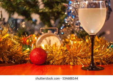 Christmas and New Year celebration holiday clock with glass of white wine and red ball covered with yellow fir